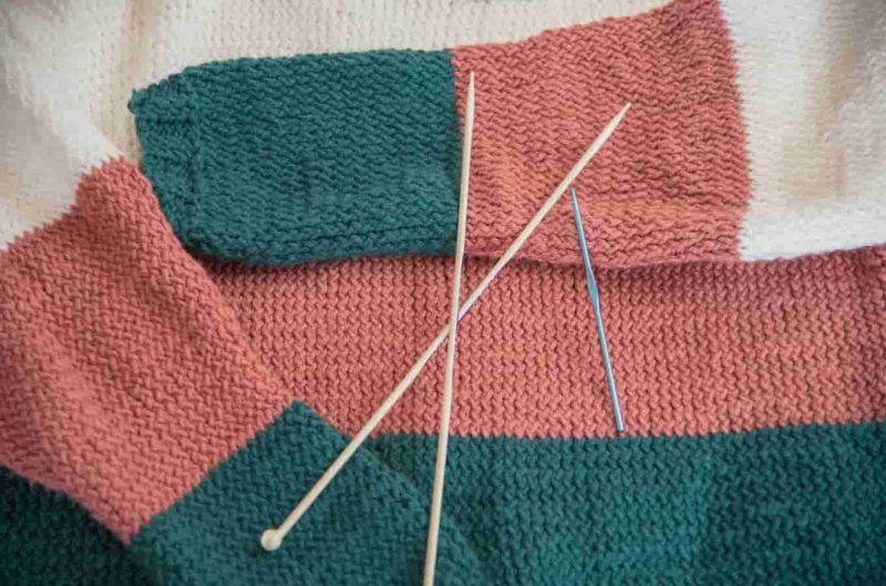 Jumper and knitting needles
